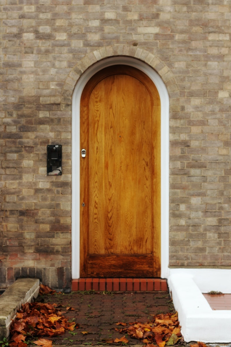arched wood door with light stain and silver hardware on a brick facade.
