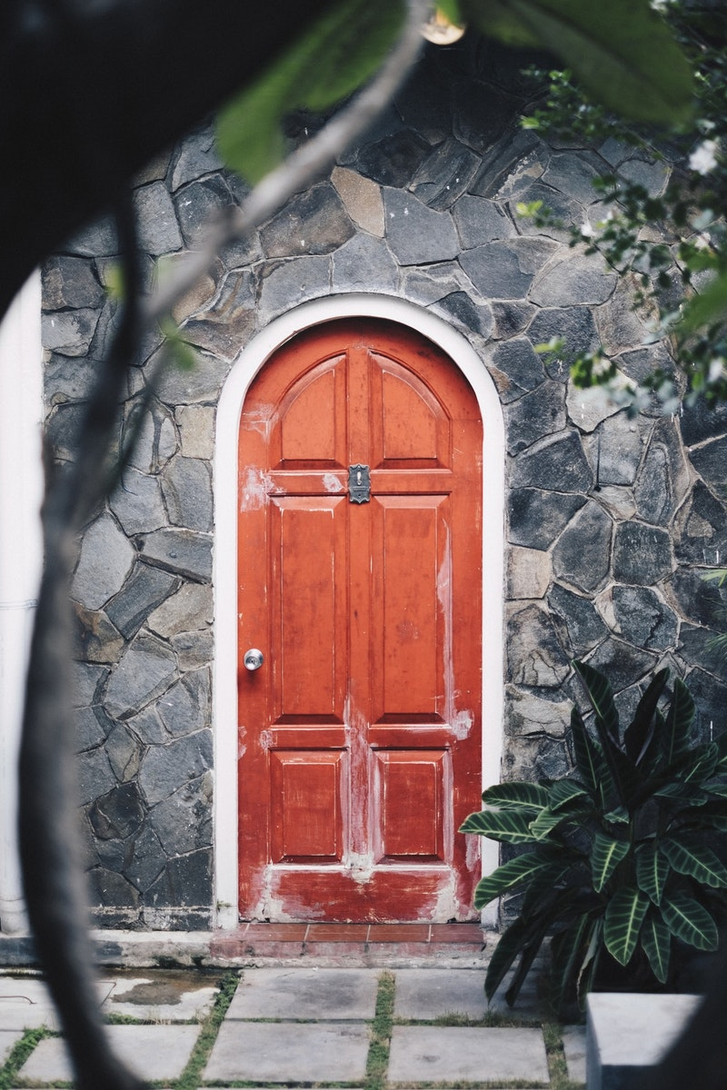 arched wood door painted red with silver hardware and six panels