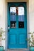 Wood door painted blue with double glass panes and black hardware.