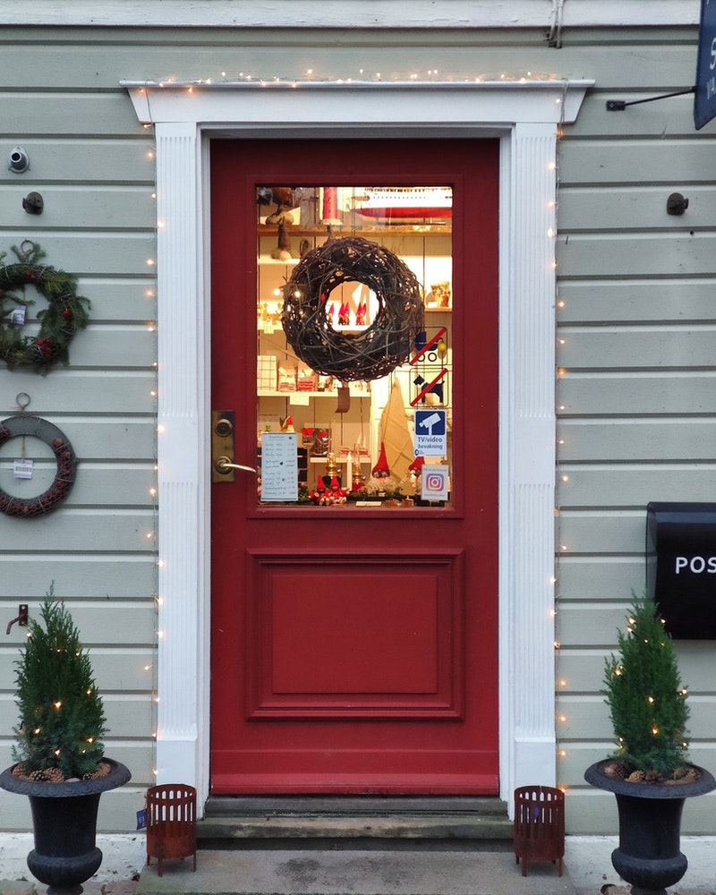 Wood door painted red with one large glass pane and decorated with signs and lights.