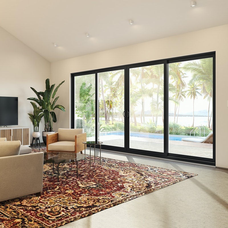 Modern MI Windows 1600 Series sliding doors in a quad configuration in a tropical home.