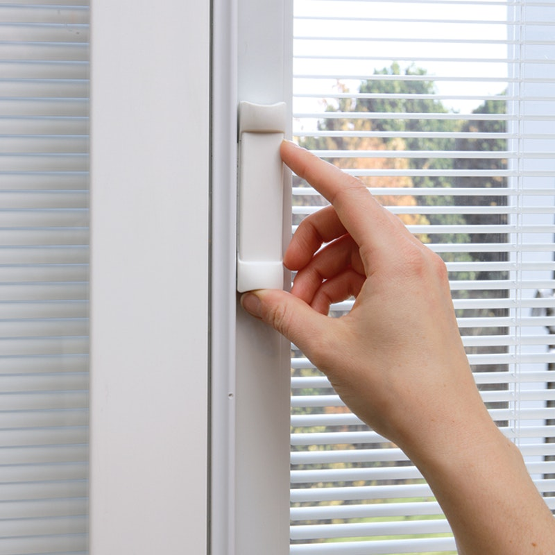Person unlocking a MI Windows sliding door with white handle hardware.