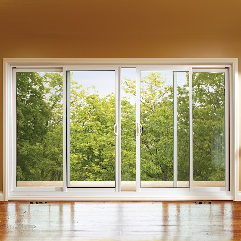 Triple panel MI windows 1600 sliding door in a room with shiny wood floors.