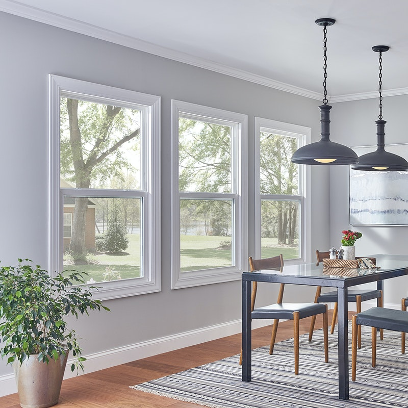 White and brightly lit dining room with three single hung windows with white finish.