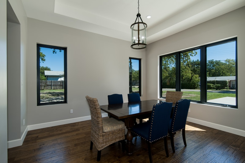 Interior view of Andersen 100 Series black fibrex picture and casement windows in a dining room.