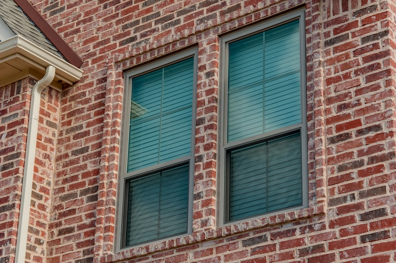Close-up of clay colored windows in brick wall of house.