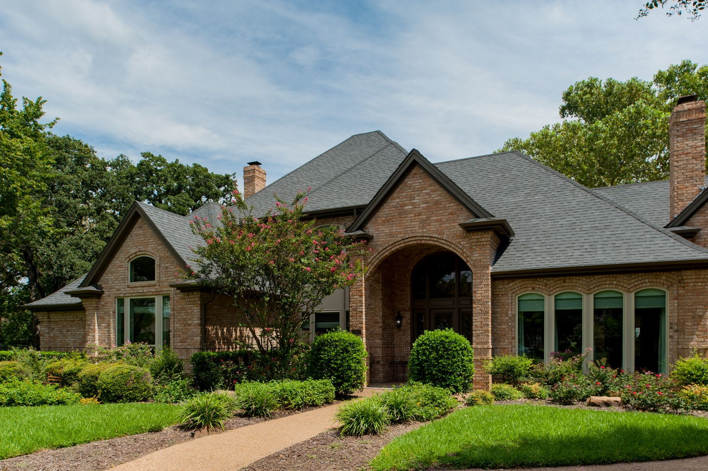 Brick suburban home with arches and almond color windows.