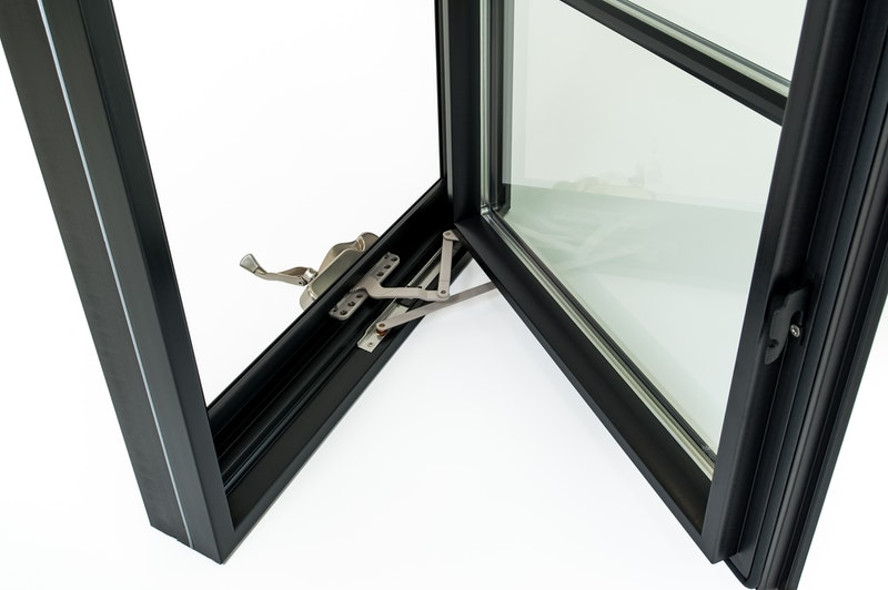 Close-up of Andersen 100 series black Fibrex casement window open to view crank handle hardware.