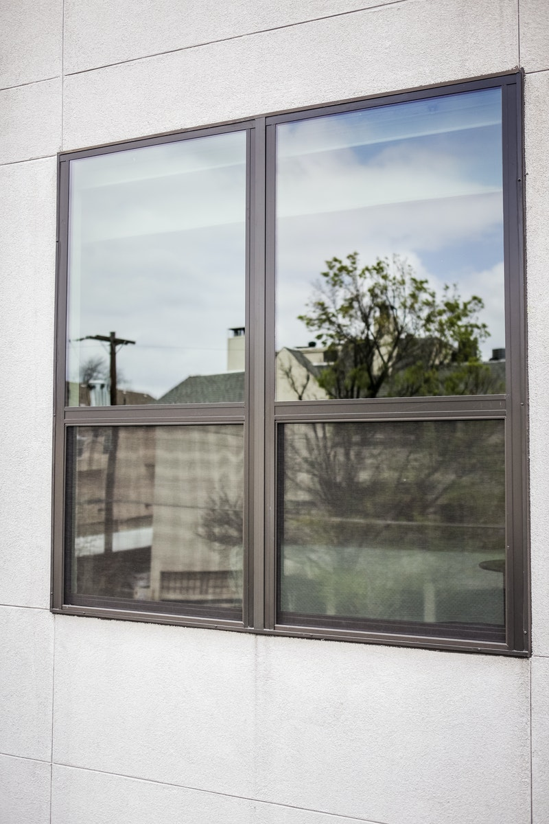 Two black windows side by side on gray stucco building.