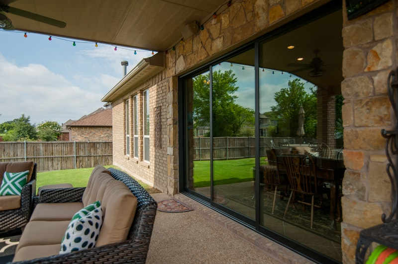 Photo of rear of house with three panel stacking patio door.