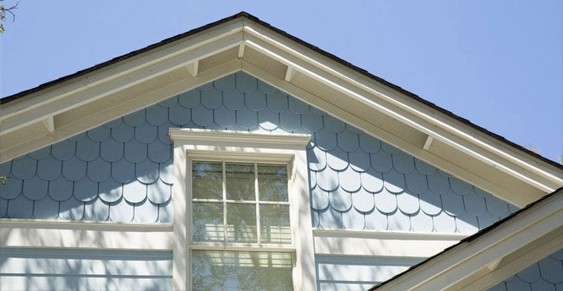 Close-up of house with white trim and light blue scallop shingles.