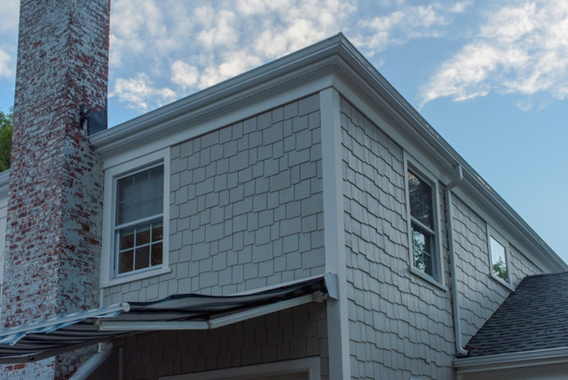 House with gray shake shingles and discolored red brick chimney.