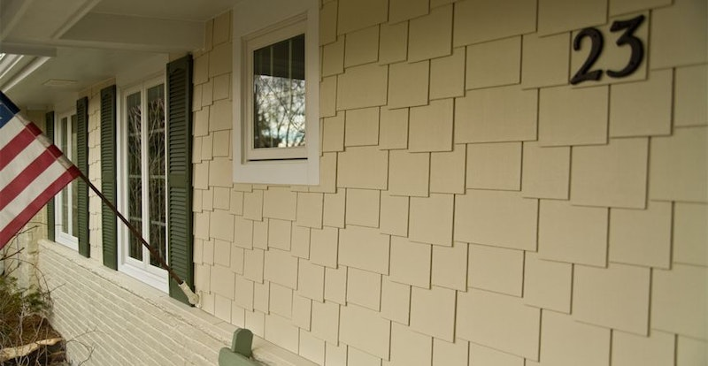 Staggered cedar shake on house with brick on lower half.