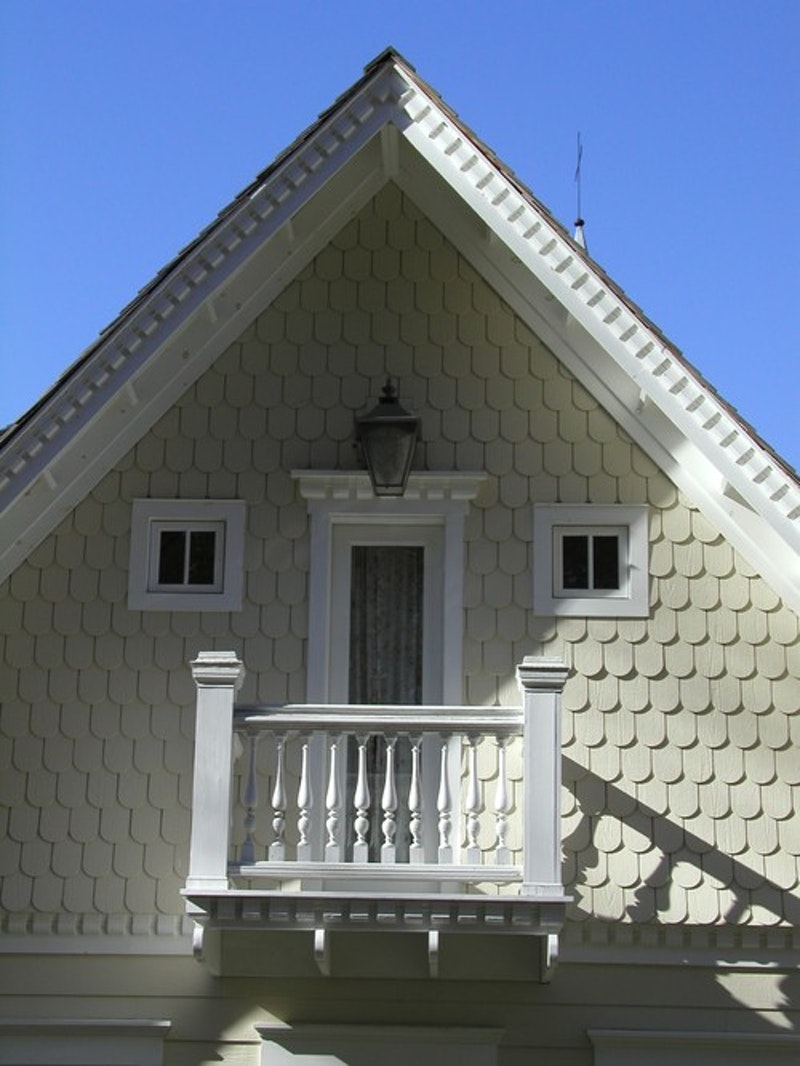 House with decorative trim, windows, juliet balcony, and scallop shingles on the gable.