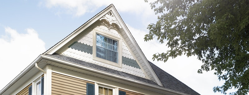 Close-up of gable with scalloped siding in white and blue.