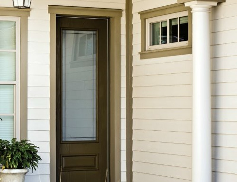 Close-up of house with cream lap siding and tan trim.