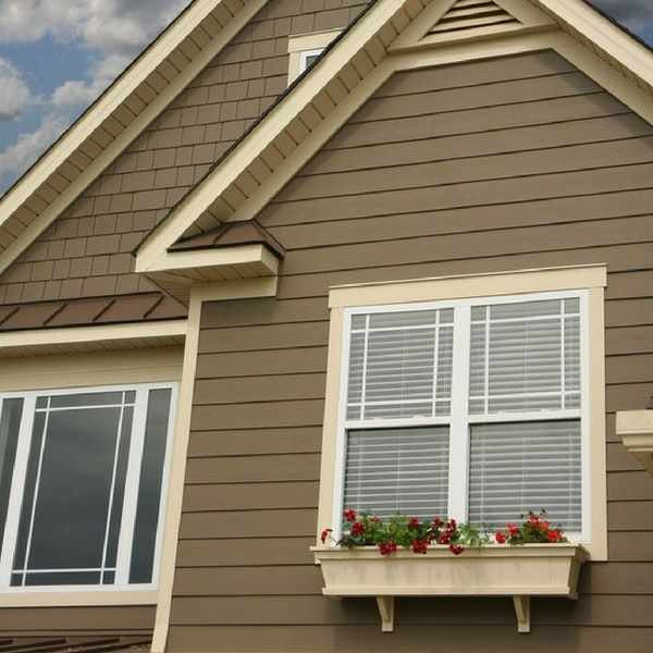 Cream-colored trim around white windows with prairie grids on home with brown siding exterior