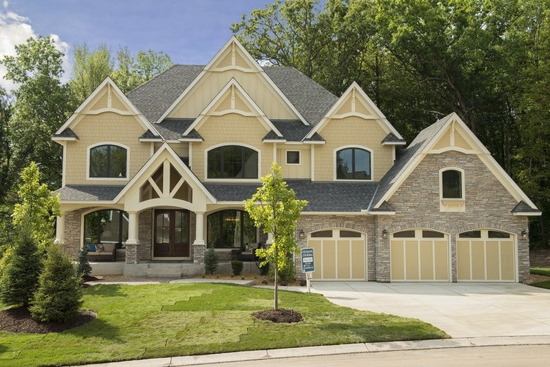 Soft-yellow house with multiple gables, three car garage, and mixed-material facade.