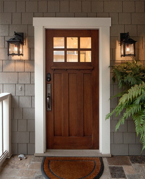 Woodgrain front door with metal hardware, white trim, and gray shake siding
