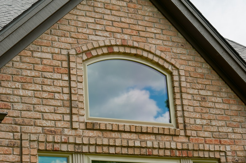 Eyebrow replacement picture window installed in brick wall.