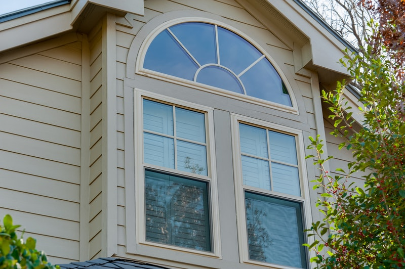 Half round window over two single hung windows on tan house with lap siding.