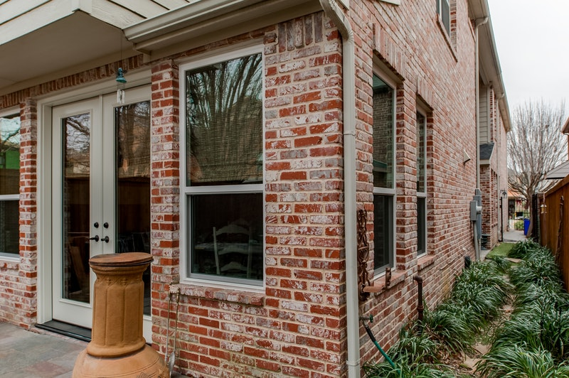 Brick house with tan single hung windows and double french doors.