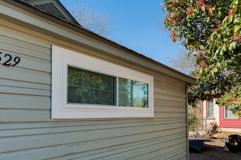 White sliding windows in house with lap siding.
