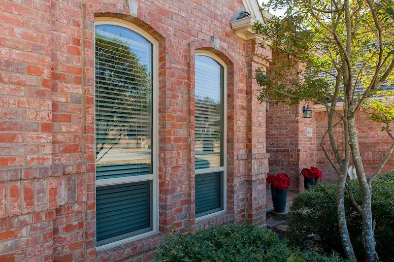 Red brick house with single-hung eyebrow windows.