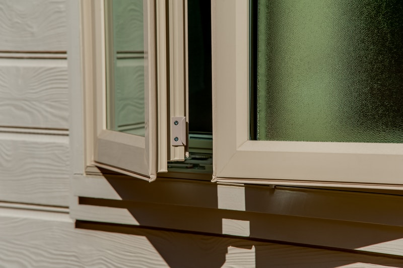 Close-up of open casement windows with textured privacy glass.