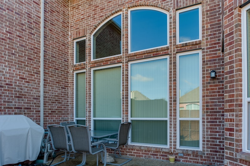 House with brick exterior and white picture windows with large hung windows below.