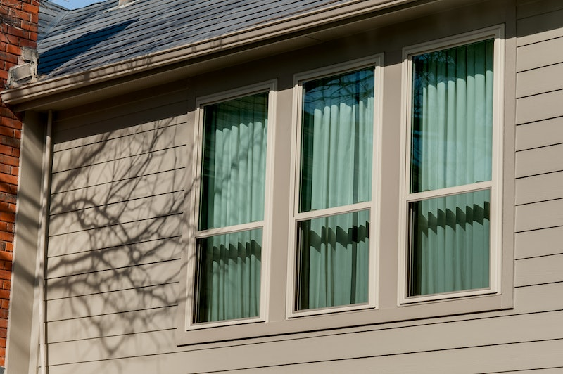 Close-up of three tan windows in house with tan lap-siding.