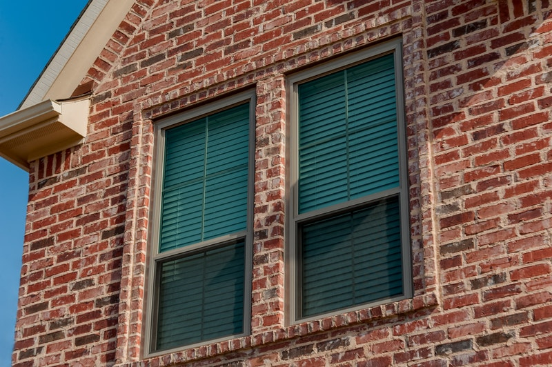 Close-up of two clay double hung windows on house with brick veneer.