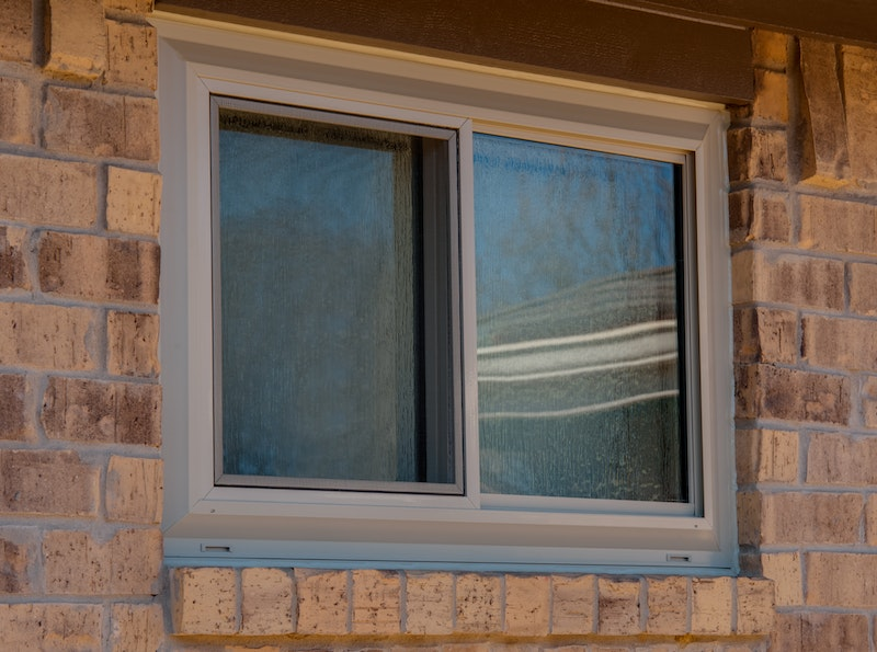 Close-up of tan sliding window on house with light brown brick.