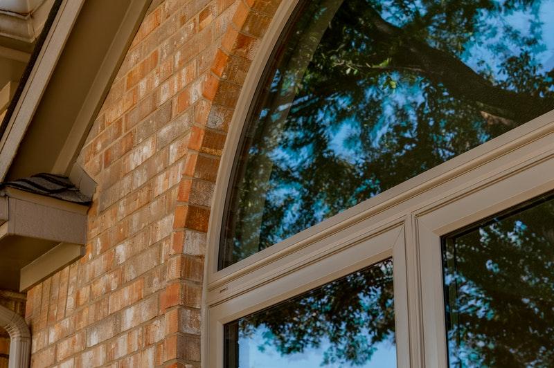 Close-up of round top window over two casement windows.