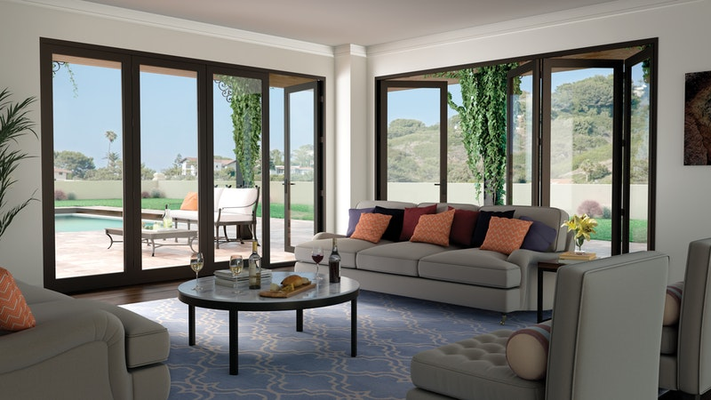 Two bronze bi-folding glass wall door systems in living room.