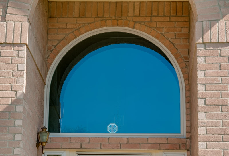 Close-up of large round top picture window.
