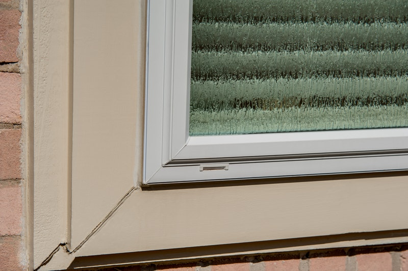 Close-up of white vinyl window with textured privacy glass.