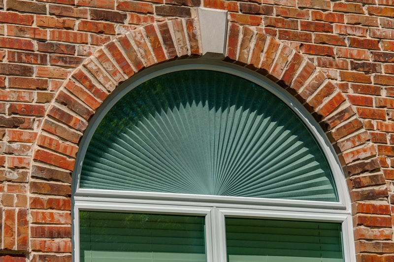 Half round picture window above two windows in red brick wall.
