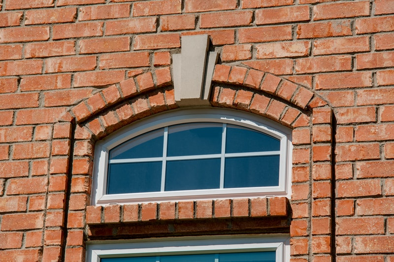 Red brick wall with white eyebrow window with grids.