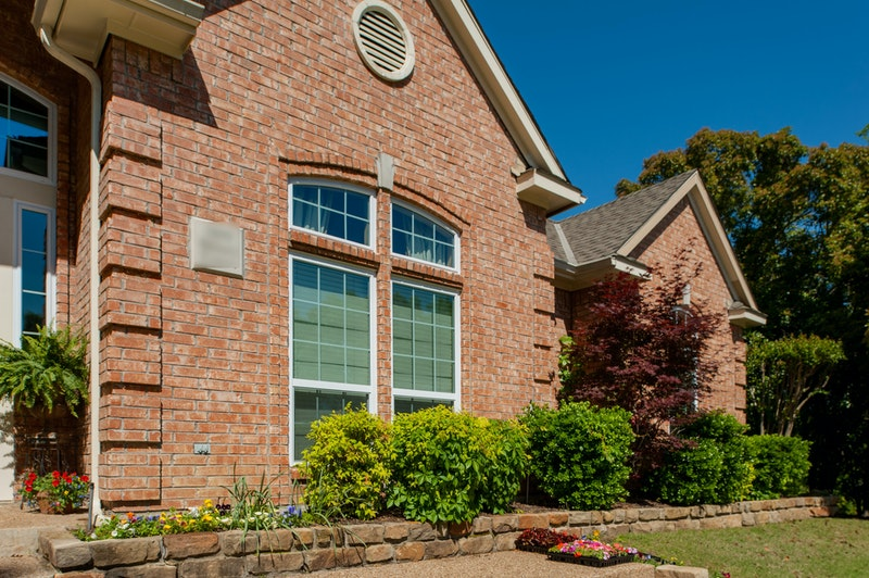 Brick house with white vinyl windows.