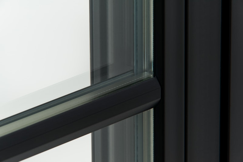 Close-up of contemporary grids on Andersen 100 Series black Fibrex casement window.