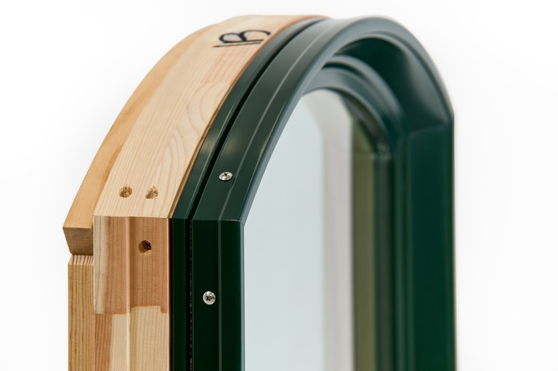 Close-up of top part of Andersen 400 Series replacement window in eyebrow style with green exterior and  pine wood interior.