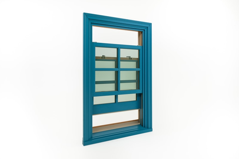 Full view of bright blue wood double hung window with both sashes open.