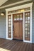 Custom wood front door with dark hardware, glass with grids on top part of door, sidelites and transom with grids