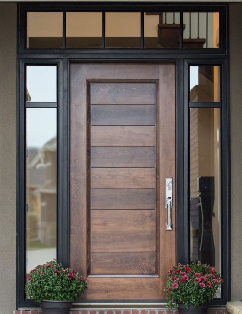 Custom wood entry door with horizontal panels across center of door panel, black door trim, clear glass transom and sidelites