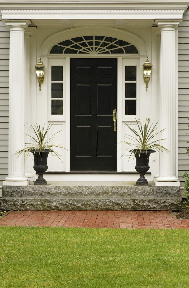 Black front door with brass hardware, white sidelites, and light colored siding.
