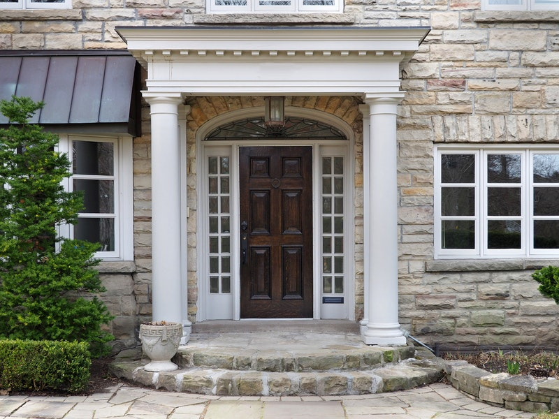 Elegant stone front entry with dark wood door, white sidelites and transom.