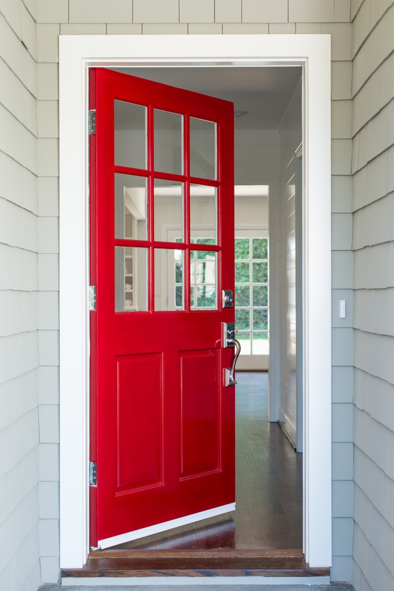 Open front door entrance featuring wood front door with red finish and grids.