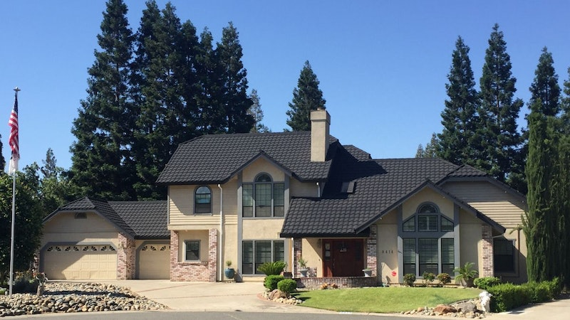 Large home with Tilcor roof tiles in Firenze. The home has neutral stucco siding and dark trim.