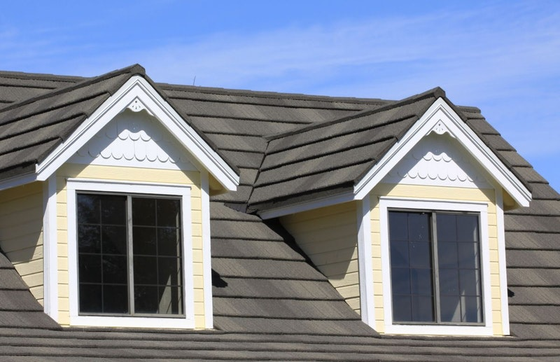 Tilcor metal roof tiles in Ironstone atop a home with yellow vinyl siding and white vinyl windows.